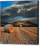 Landscape Of Hay Bales In Front Of Mountain Range With Dramatic  Canvas Print