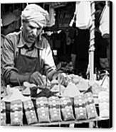 Local Arab Man Measuring Out A Quantity Of Spice For Sale On Stall Of Spices At The Market In Nabeul Tunisia Canvas Print by Joe Fox
