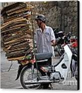 Man Carrying Cardboard On The Back Of His Scooter Canvas Print by Sami Sarkis