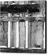 old patched up wooden fence using old bits of wood in snow Forget Canvas Print