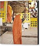 Woman Carrying Cow Dung In Basket On Canvas Print by Paul Miles