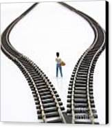 Figurine Between Two Tracks Leading Into Different Directions Symbolic Image For Making Decisions. Canvas Print