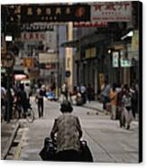 An Elderly Woman Pushes A Cart Canvas Print by Justin Guariglia