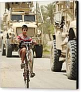 An Iraqi Boy Rides His Bike Past A U.s Canvas Print by Stocktrek Images