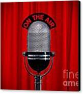 Microphone On Stage With Spotlight On Red Curtain Canvas Print by Richard Thomas