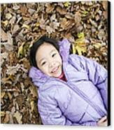 Smiling Girl Lying On Autumn Leaves Canvas Print