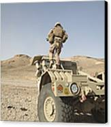 Soldier Climbs A Damaged Husky Tactical Canvas Print by Stocktrek Images