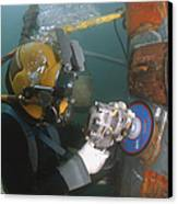 U.s. Navy Diver Uses A Grinder To File Canvas Print by Stocktrek Images