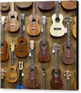 Various Guitars & Ukuleles Hanging From Wall Canvas Print