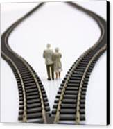 Figurines Between Two Tracks Leading Into Different Directions Symbolic Image For Making Decisions. Canvas Print