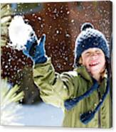 A Boy Throws A Snowball While Playing Canvas Print