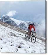 A Mountain Biker Rides Through The Snow Canvas Print