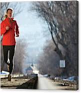 A Woman Running Near A Railroad Track Canvas Print