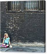 Girl Sitting On Ground Next To Brick Wall Canvas Print
