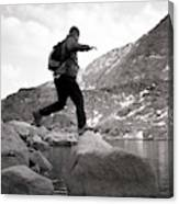A Man Jumps From One Rock To Another Canvas Print