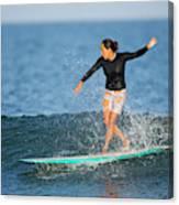 A Woman Rides A Wave On A Longboard Canvas Print