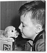 A Young Boy Is Face To Face With A Puppy Tongue. Canvas Print