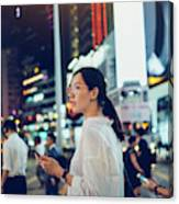 Beautiful Asian woman using mobile phone while crossing road in busy downtown city street at night Canvas Print