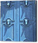 Blue Door Decorated With Wooden Animal Heads Canvas Print
