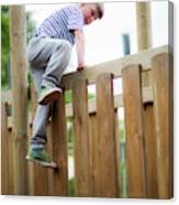 Boy Climbing Over Wooden Fence Canvas Print