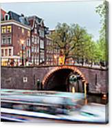 Canal Bridge And Boat Tour In Amsterdam At Evening Canvas Print