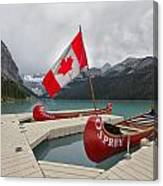 Canoes And Canada Flag At Lake Louise Canvas Print