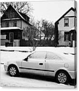 car covered in snow parked by the side of the street in front of residential homes caswell hill Sask Canvas Print