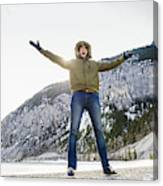 Caucasian man cheering in snowy field Canvas Print