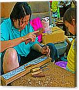 Child Watches As Mom Works In Teak Wood Carving Shop In Kanchanaburi-thailand Canvas Print