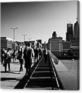 commuters and city workers cross london bridge over the river thames in the morning central London England UK Canvas Print