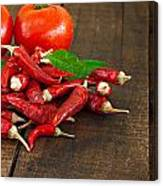 Dried Red Chillies And Tomato On A Rustic Wooden Table Canvas Print
