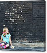 Girl Sitting On Ground Next To Brick Wall Canvas Print