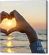 Heart shaped hands framing ocean sunset Canvas Print