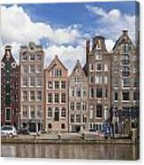 Historic Buildings Along The Damrak Canal In Amsterdam Canvas Print