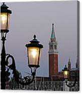 Lampposts Lit Up At Dusk With Building Canvas Print