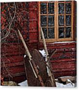 Old Wheelbarrow Leaning Against Barn In Winter Canvas Print