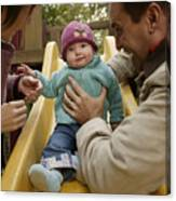 Parents With Baby Playing On Slide Canvas Print