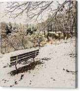 Park Bench In The Snow Covered Park Overlooking Lake Canvas Print