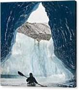 Sea Kayaker Paddles Through An Ice Cave Canvas Print