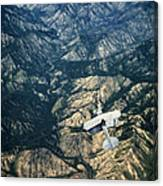 Small Plane Flying Over Mountains Canvas Print