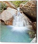 Small Waterfall Casdcading Over Rocks In Blue Pond Canvas Print