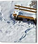 Snowy Foot Prints Around Snow Covered Park Bench Canvas Print