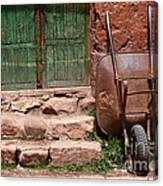 Rusty Wheelbarrow And Green Door Canvas Print