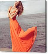 Young Woman In Orange Dress Flying In The Wind At Sea Shore Canvas Print