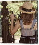 Girl Looking Over Iron Gate Canvas Print