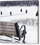 Ice Skates Hanging On Bench With People  Skating In Background Canvas Print