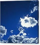 Sunlit Fluffy White Clouds In A Blue Canvas Print