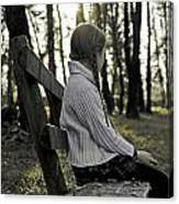 Girl Sitting On A Wooden Bench In The Forest Against The Light Canvas Print