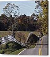 A Hilly Country Road Passes A Fenced Canvas Print