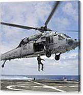 A Naval Aircrewman Is Hoisted Into An Canvas Print